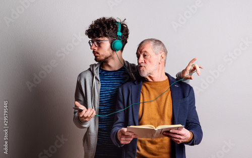Studio shot of young versus old generation, technology addiction concept. - 295795445