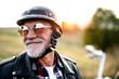 Leinwandbild Motiv A cheerful senior man traveller with motorbike in countryside, headshot.