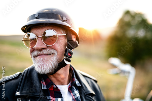 A cheerful senior man traveller with motorbike in countryside, headshot.