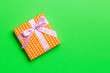 canvas print picture - wrapped Christmas or other holiday handmade present in paper with pink ribbon on green background. Present box, decoration of gift on colored table, top view with copy space