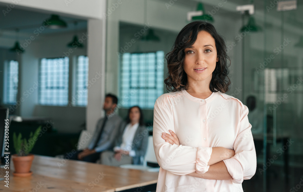 Fototapeta Smiling young businesswoman standing confidently in a large office