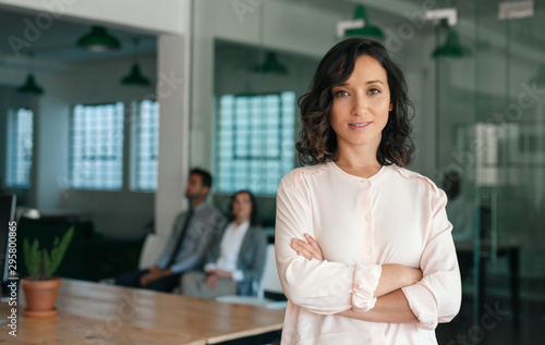 Photo  Smiling young businesswoman standing confidently in a large office