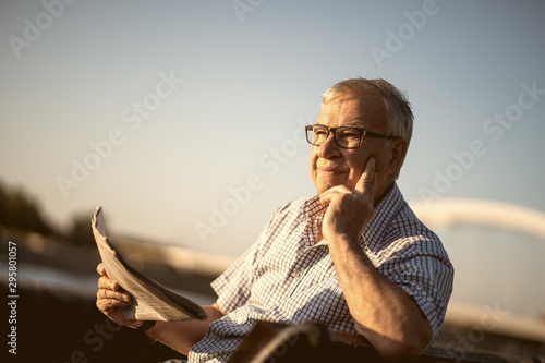 Fotomural  Outdoor portrait of senior man who is reading newspapers.