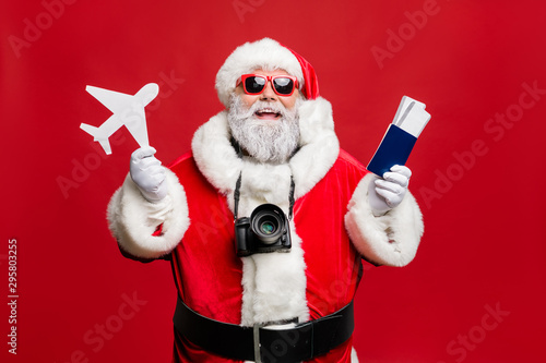 obraz PCV Portrait of funny hipster santa claus have journey abroad in terminal want travel take photo photigraphing wear spectacles eyewear eyeglasses costume isolated over red background