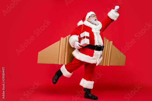 obraz lub plakat Full length profile side photo of excited elderly super christmas father travel launch fly up to give presents on noel night wear card board wings cap hat isolated over red background