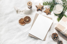 Christmas Blank Greeting Card Mock-up Scene. Festive Winter Wedding Composition. Craft Envelope, Pine Cone, Gift Box, Orange Fruit Slices And Fir Tree Branch On White Table, Linen Background. Flat Lay