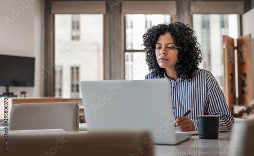 Young female entrepreneur working on her laptop at home Fototapete
