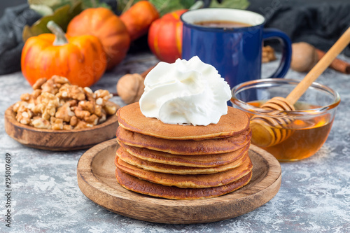 Fotografie, Obraz Delicious homemade pumpkin pancakes served with whipping cream, walnuts and hone