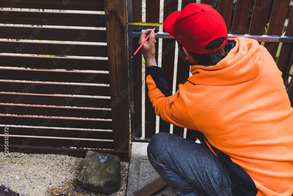 Fototapety, obrazy: tradesman taking measures and preparing timber to be cut to build a fence
