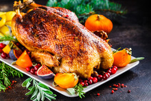 Christmas Baked Duck With Herbs And Fruits On Gray Plate, Dark Background.