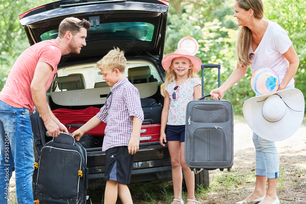 Fototapety, obrazy: Family and children carry suitcases to the car