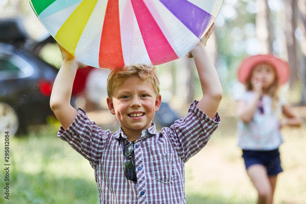 Fototapety, obrazy: Boy playing with a colorful ball