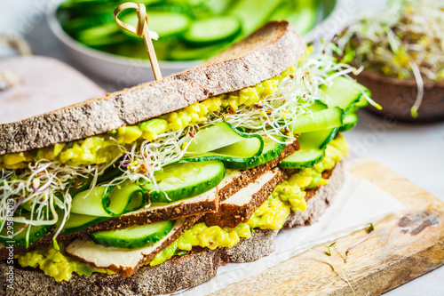 Fototapeta Big veggie sandwich with tofu, vegetables, sprouts and guacamole. Healthy vegan food concept. obraz