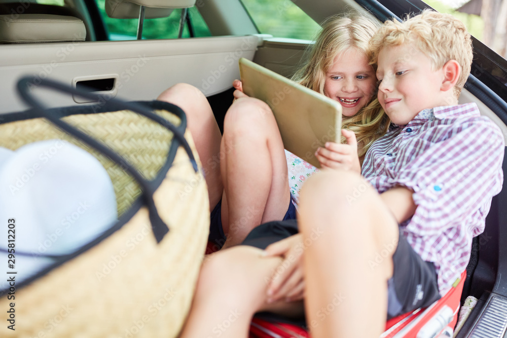 Fototapety, obrazy: Two kids in the car with tablet computer