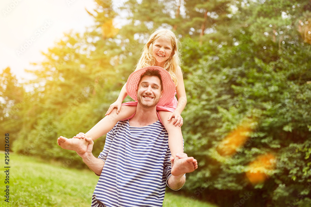 Fototapety, obrazy: Father is riding piggyback daughter in the garden