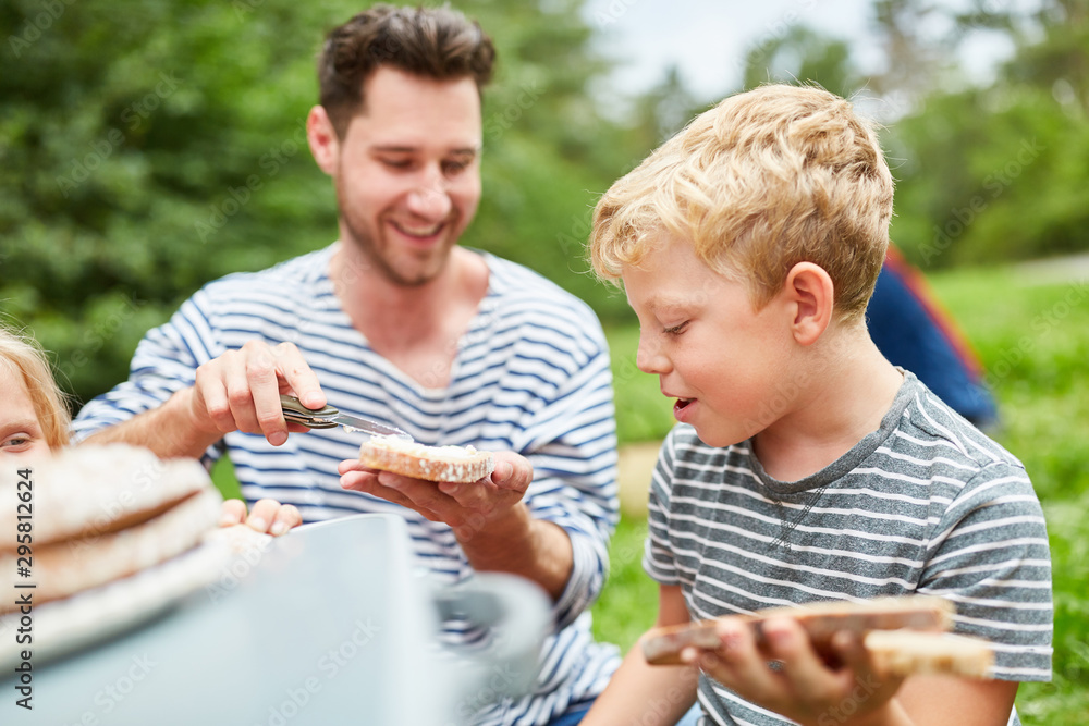 Fototapety, obrazy: Boy smearing at the bread for a picnic