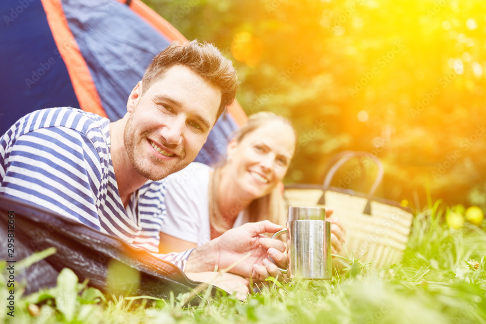 Fototapety, obrazy: Couple drinking coffee in tent while camping