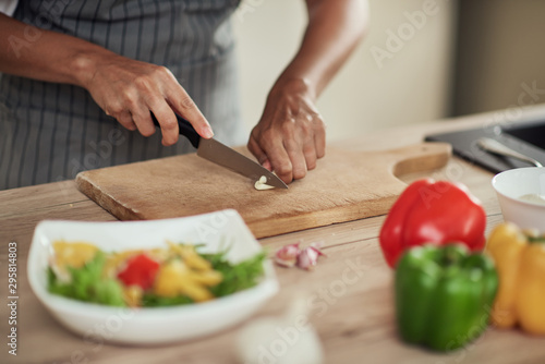 Close up of mixed race woman in apron standing in domestic kitchen and cutting garlic Fototapeta