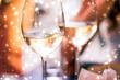 Leinwandbild Motiv Winter holiday glasses of white wine and glowing snow on background, Christmas time romance