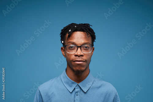 Fotografiet Head and shoulders portrait of young African-American man looking at camera whil
