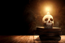 Pile Of The Book With A Human Skull And Candlelight On A Wooden Table