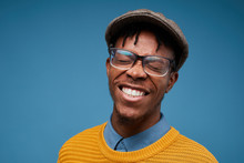 Head And Shoulders Portrait Of Excited African-American Man Smiling Happily While Posing Against Blue Background Wearing Bright Knit Sweater