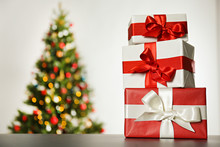 Festive Composition With Stack Of Many Different Presents In Colorful Wrapping Paper On Foreground And Blurry Decorated Christmas Spruce Tree On Background. Close Up, Copy Space.