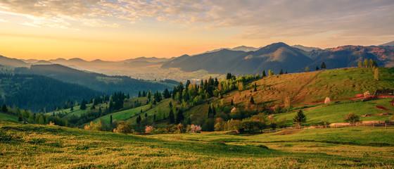 Beautiful landscape mountain hill meadow sunrise morning village Bucovina Romania