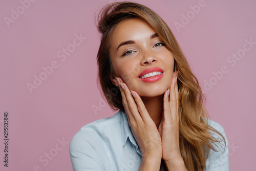 Fototapeta  Photo of lovely young female model touches gently chin with both hands, smiles g