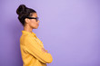 Leinwanddruck Bild - Profile photo of pretty dark skin business lady with crossed arms looking empty space serious wear specs yellow shirt isolated purple color background