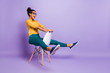 Leinwanddruck Bild - Full body profile photo of amazing dark skin lady sitting on chair between legs like driving car wear specs yellow shirt trousers isolated purple color background