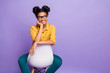Leinwanddruck Bild - Photo of amazing dark skin lady sitting cozy on chair looking wondered side empty space wear specs yellow shirt trousers isolated purple color background