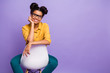 Leinwanddruck Bild - Photo of amazing dark skin lady sitting cozy on chair between legs looking positive on camera wear specs yellow shirt trousers isolated purple color background