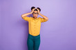 Leinwanddruck Bild - Photo of amazing pretty dark skin lady holding hands on head not believe awful news open mouth wear specs yellow shirt pants isolated purple color background