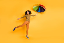 Full Length Body Size Photo Of Wavy Cheerful Cute Nice Charming Pretty Girlfriend Flying With Umbrella Wearing Orange Pants Trousers Footwear Isolated Over Vivid Yellow Color Background