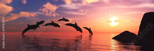 Obraz na plátne Playing dolphins at sunset. Seascape with dolphins.