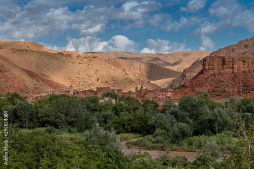 Moroccan berber village with mountains, river, desert, mountains and lush vegetation