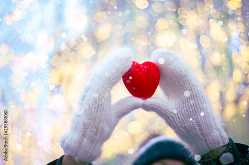 Obraz Woman hands in white knitted mittens with a red heart on a snow background. - fototapety do salonu