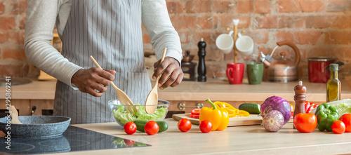 Obraz na plátně  Man cooking fresh healthy vegetables salad at kitchen