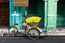 Horizontal Shot Of A Yellow Cycle Rickshaw In Georgetown, Malaysia