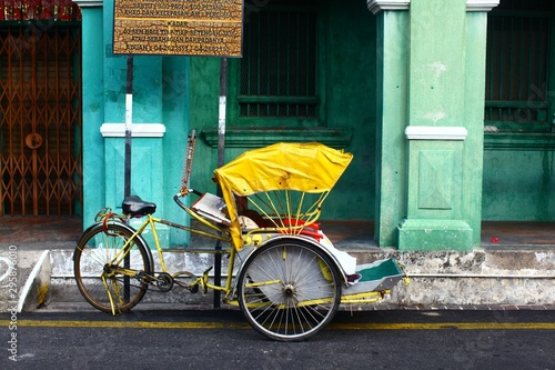 Fototapeta Horizontal shot of a yellow cycle rickshaw in Georgetown, Malaysia