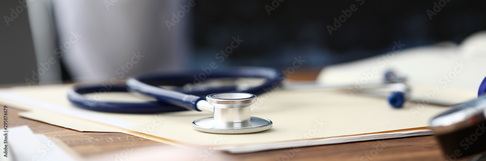 Fototapeta Medical stethoscope head lying at paper document on table