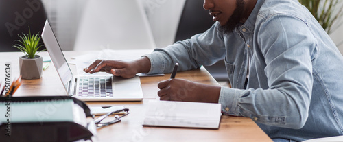 Fototapeta African American worker noting information from laptop in office obraz
