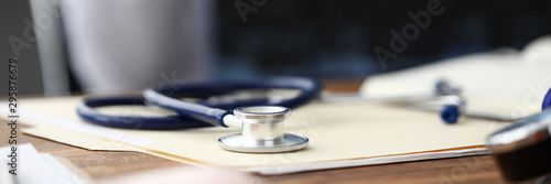Stampa su Tela  Medical stethoscope head lying at paper document on table