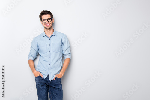 Fototapeta Photo of cheerful funky positive intelligent man smiling toothily holding hands in pockets isolated over grey color background obraz