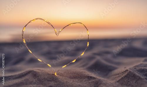 Obraz Heart shape made of led lights at the beach sand - fototapety do salonu