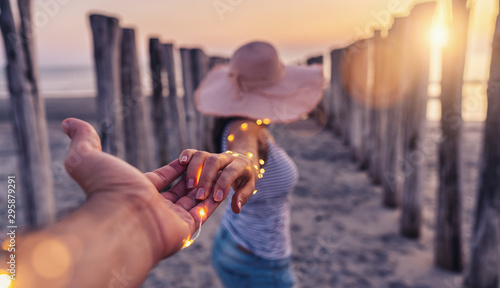 Stickers pour portes Fleur Couple holding hands and walking on beach in sunset, woman with white shirt and shorts jeans