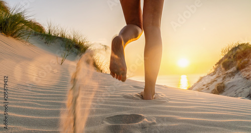Fotobehang Oranje Woman runs towards to the Baltic Sea Beach at Sunset