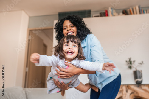 Obraz Mother playfully swinging her little daughter in the air - fototapety do salonu