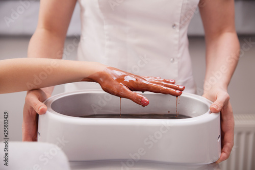 Carta da parati Female hand in beauty spa  salon with paraffin wax in bowl held by beautician therapist